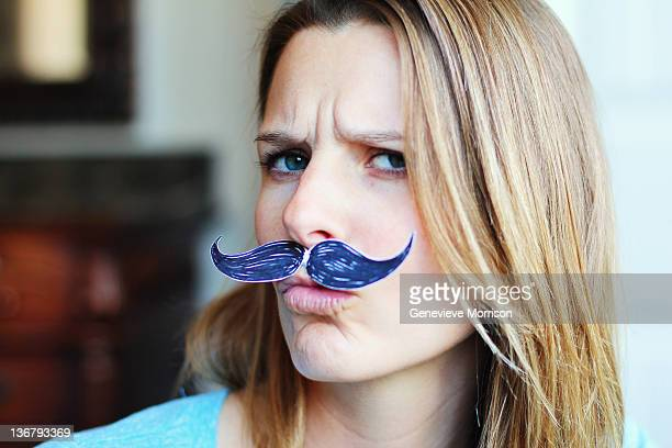 Young woman wearing fake mustache