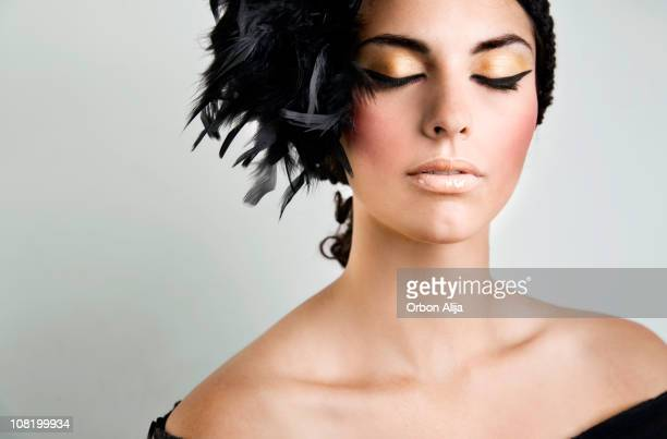 Young Woman Wearing Feather Hat and Make-Up Closing Eyes