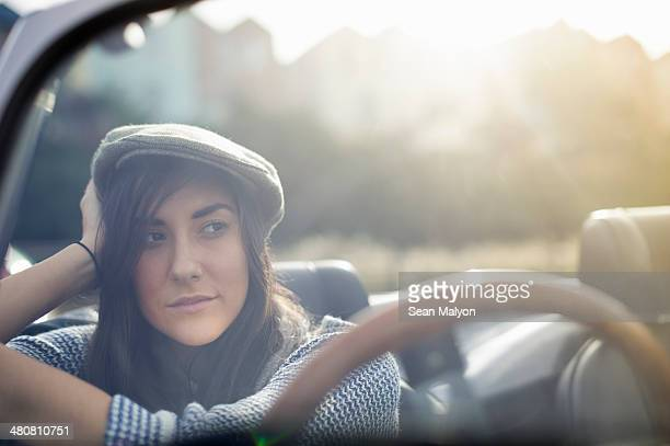Young woman wearing flat cap in convertible