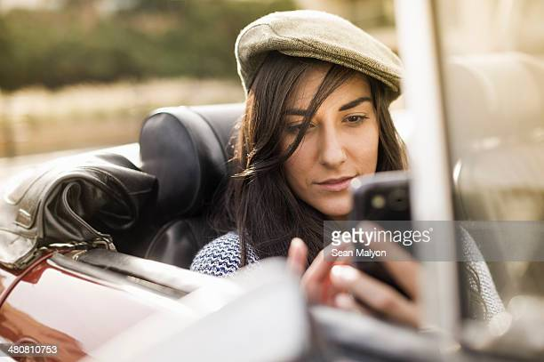 young woman wearing flat cap in convertible using smartphone - sean malyon stock pictures, royalty-free photos & images