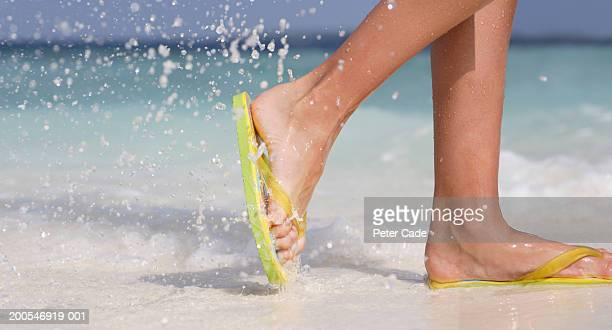 young woman wearing flip-flops walking on beach, low section - open toe stock pictures, royalty-free photos & images