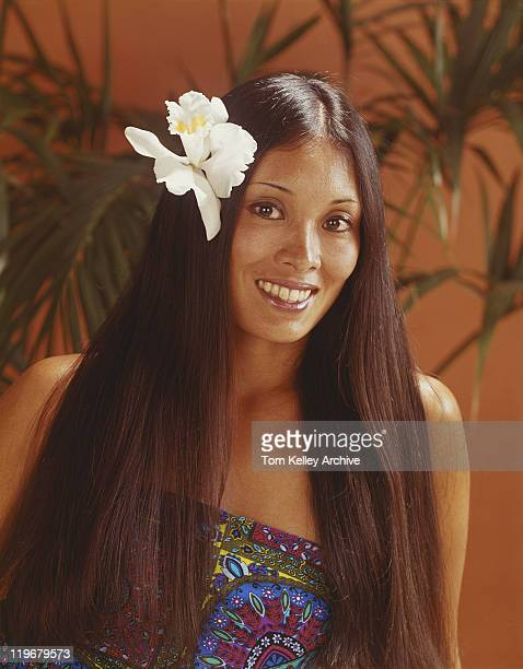 young woman wearing flower in hair, smiling, portrait - 1980 bildbanksfoton och bilder