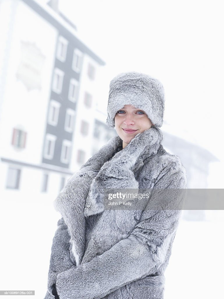 Young woman wearing fur hat and jacket, smiling, portrait : Stockfoto
