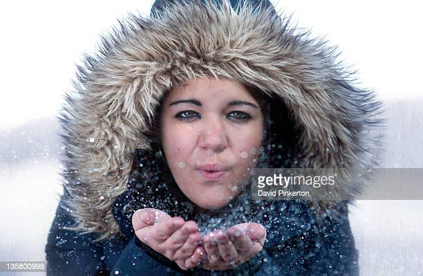 young woman wearing fur trimmed coat blowing snow - fur trim stock pictures, royalty-free photos & images