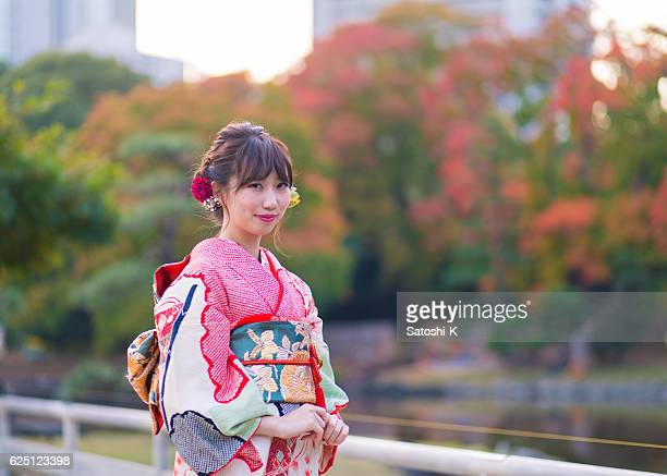 young woman wearing furisode in autumn foliage - seijin no hi stock pictures, royalty-free photos & images