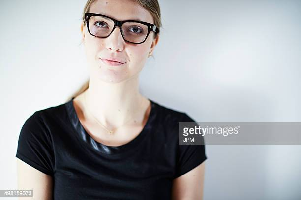 Young woman wearing glasses and black top, studio shot