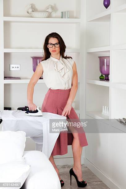 Young woman wearing glasses ironing shirt