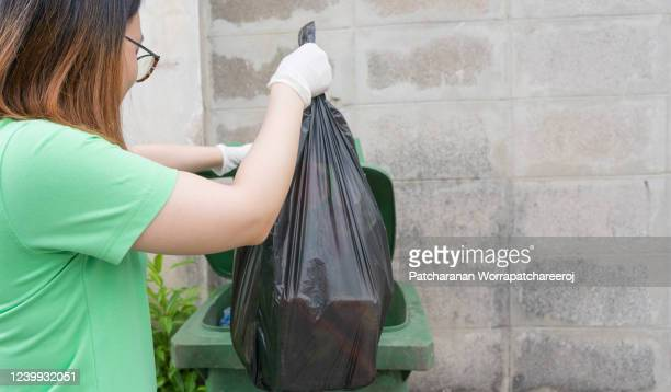 a young woman wearing gloves and carrying a black garbage bag into the trash. - ゴミ袋 ストックフォトと画像