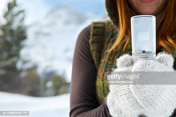 Young woman wearing gloves using mobile phone outdoors, mid section, close up