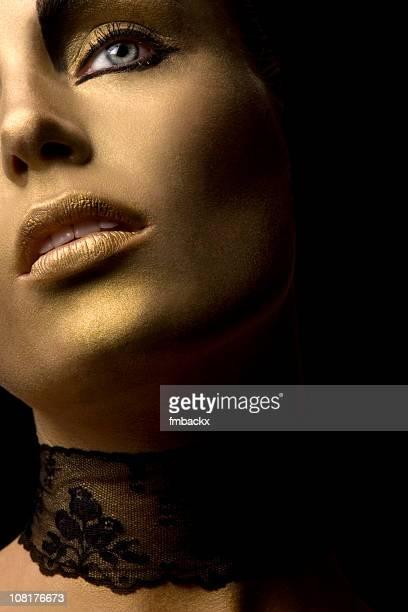 Jeune femme portant or de la peinture du visage et de dentelle