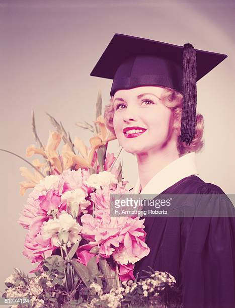 young woman wearing graduation robes and mortarboard, holding bouquet of flowers. (photo by h. armstrong roberts/retrofile/getty images) - graduation clothing stock pictures, royalty-free photos & images