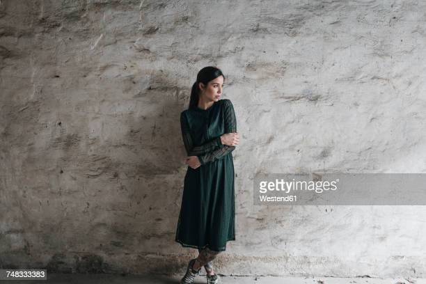 Young woman wearing green dress, staning in front of wall