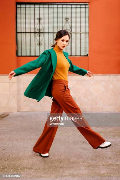 young woman wearing green jacket walking on footpath against building in city - fashionable stock pictures, royalty-free photos & images