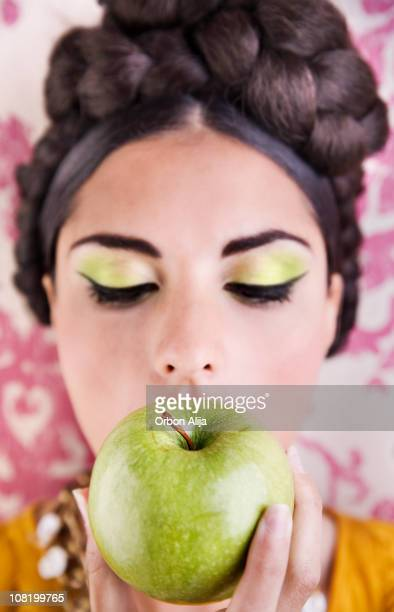 Young Woman Wearing Green Make-Up Eating Apple