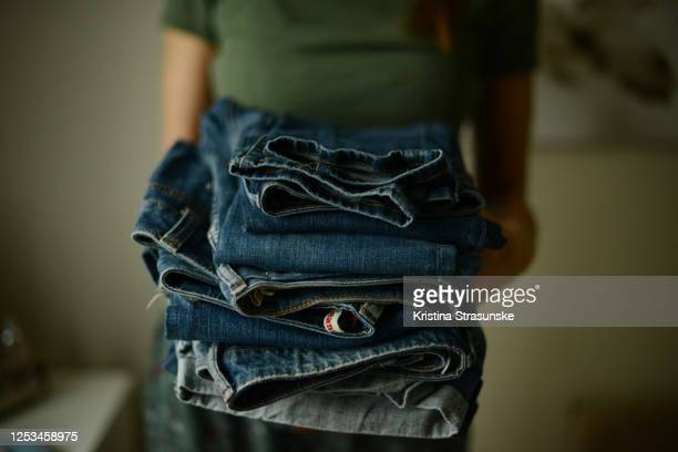 young woman, wearing green t-shirt,  holding a pile of folded jeans in her both hands - kristina strasunske stock pictures, royalty-free photos & images