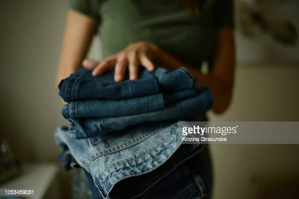 young woman, wearing green t-shirt,  holding a pile of folded jeans in her both hands - broek stockfoto's en -beelden