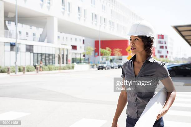 Young woman, wearing hard hat, carrying plans