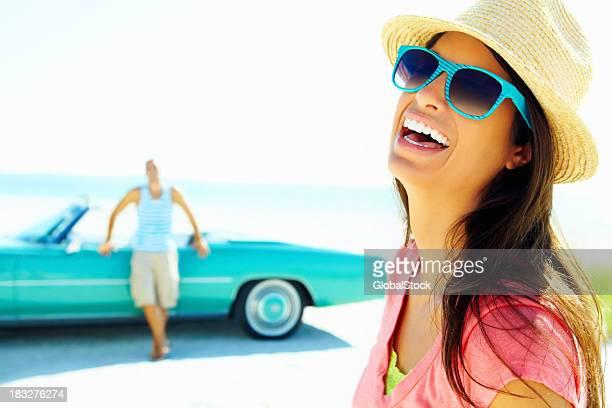 Junge Frau mit Hut und Sonnenbrille whith Mann im Hintergrund