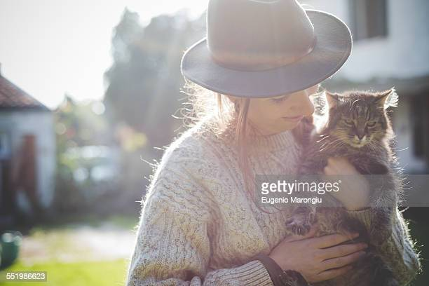 Young woman wearing hat, holding cat