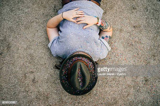 young woman wearing hat with confetti while lying on field - pauze nemen stockfoto's en -beelden