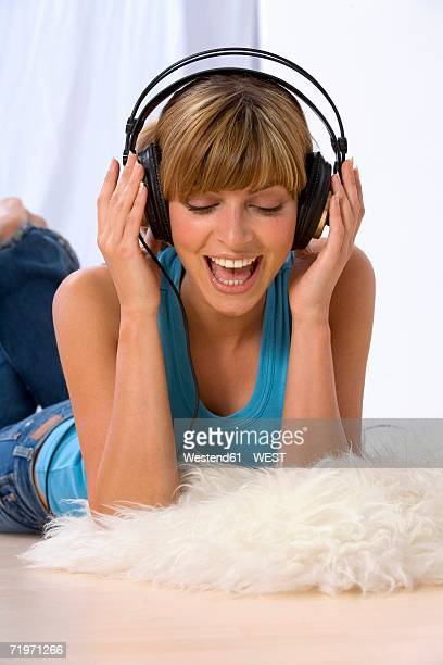 Young woman wearing head phones, looking down
