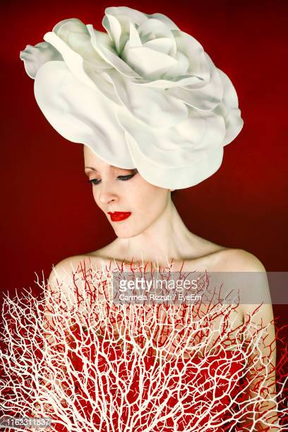 young woman wearing headdress and dress against red background - off shoulder stock pictures, royalty-free photos & images