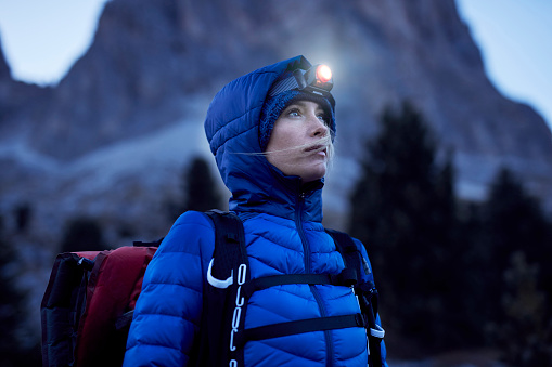 Young woman wearing headlamp at dusk in the mountains - gettyimageskorea