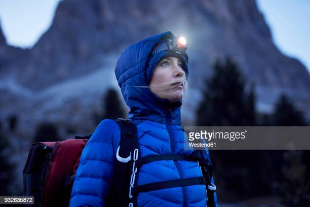young woman wearing headlamp at dusk in the mountains - avontuur stockfoto's en -beelden