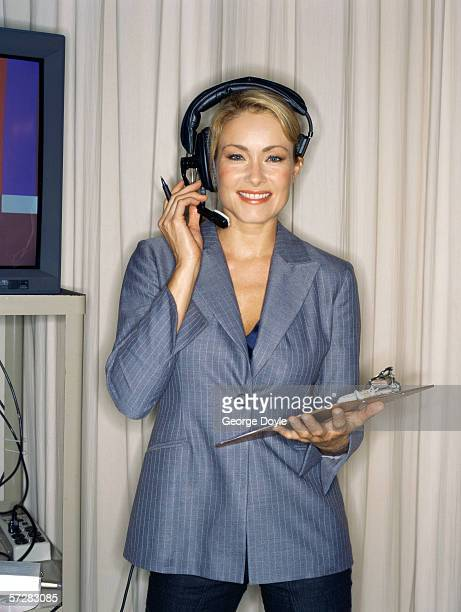 young woman wearing headphones and holding a note pad - producer stock pictures, royalty-free photos & images