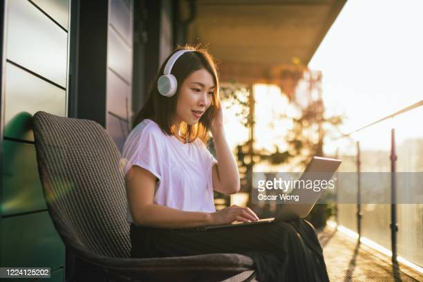 young woman wearing headphones and working with laptop on the balcony - using laptop stock pictures, royalty-free photos & images