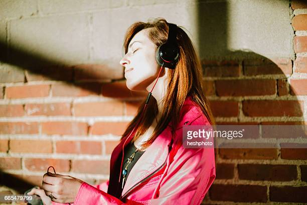 young woman wearing headphones eyes closed smiling - heshphoto fotografías e imágenes de stock