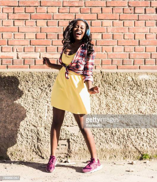 young woman wearing headphones, laughing and dancing to music
