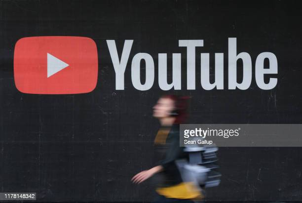 Young woman wearing headphones walks past a billboard advertisement for YouTube on September 27, 2019 in Berlin, Germany. YouTube has evolved as the...