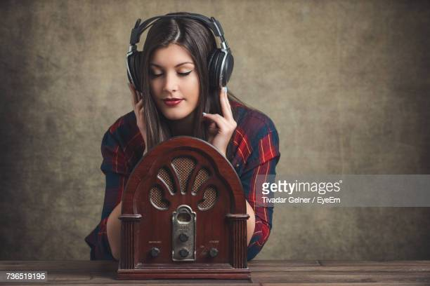 Young Woman Wearing Headphones With Old Fashioned Radio