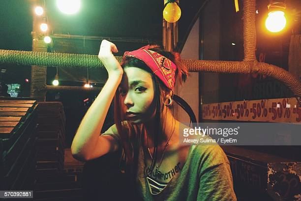 Young Woman Wearing Headscarf With Head In Hand Sitting In Illuminated Balcony