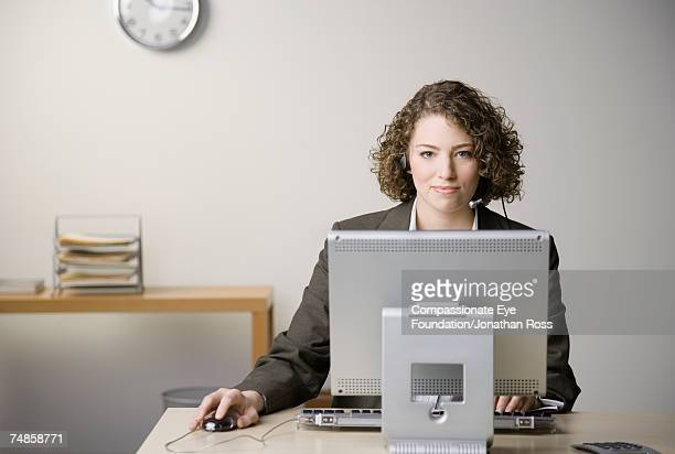 Young woman wearing headset sitting at desk in office, using computer, portrait