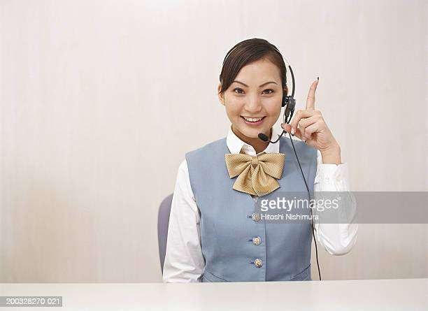 Young woman wearing headset sitting at desk, portrait