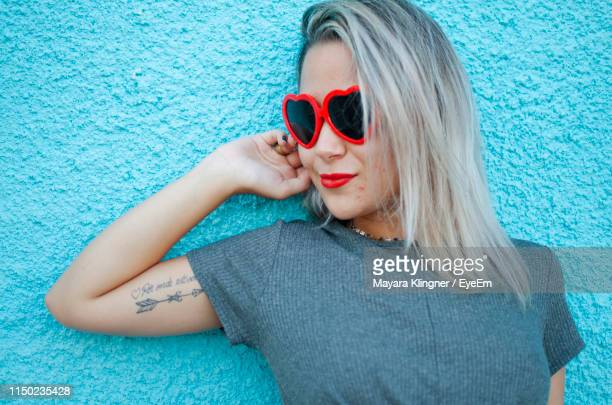 young woman wearing heart shape sunglasses against blue wall - tattoo designs hearts stock pictures, royalty-free photos & images