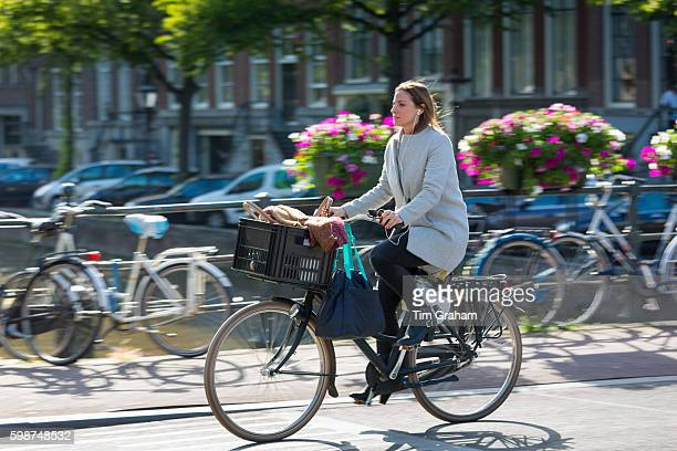 Young woman wearing high heels shoes and headphones cycling out for evening across bridge in Amsterdam Holland