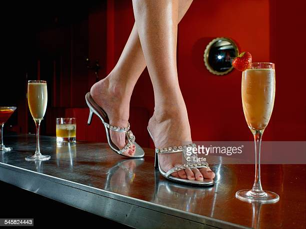 Young Woman Wearing High Heels Walking on Bar