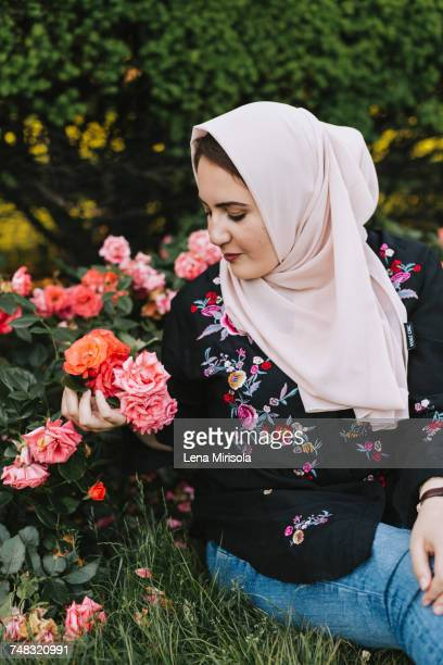 Young woman wearing hijab admiring flowers