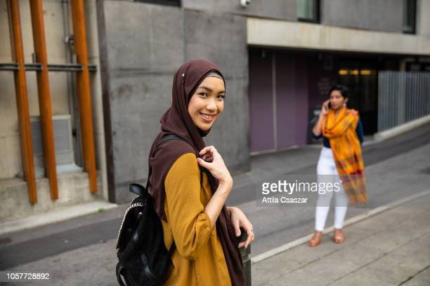 Young woman wearing hijab and smiling on street