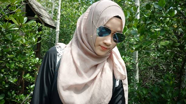 Young Woman Wearing Hijab And Sunglasses Standing Against Trees