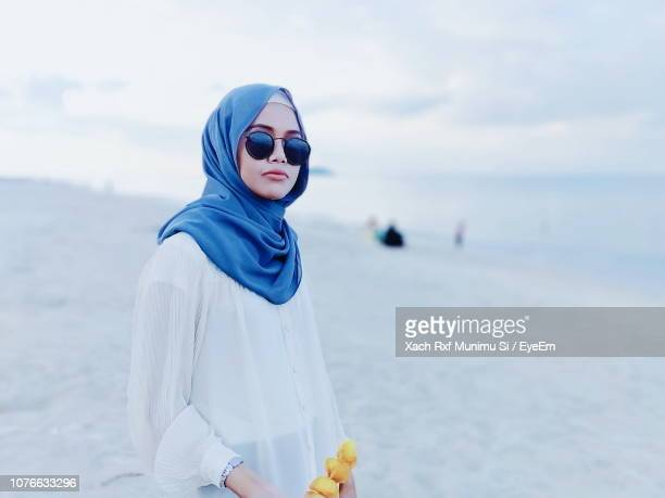 young woman wearing hijab at beach - muslim woman beach stock photos and pictures