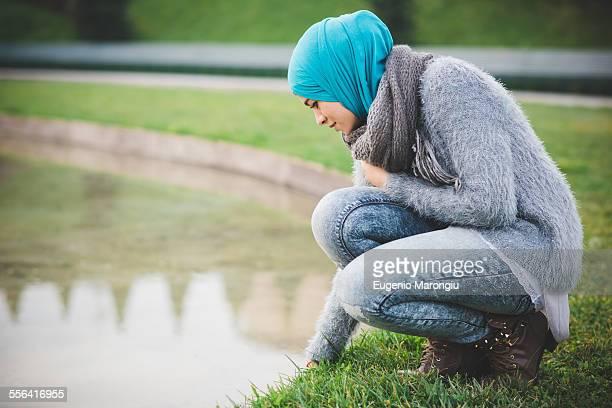 Young woman wearing hijab crouching at park lakeside