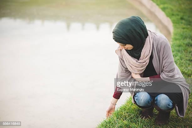 Young woman wearing hijab crouching next to park lake
