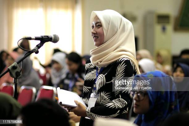young woman wearing hijab giving speech - giving stock pictures, royalty-free photos & images