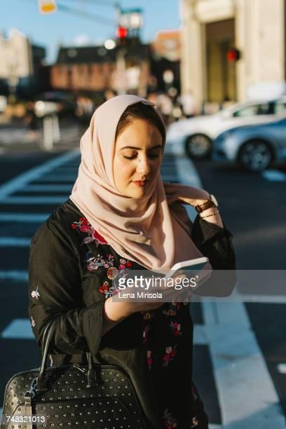 Young woman wearing hijab looking at smartphone