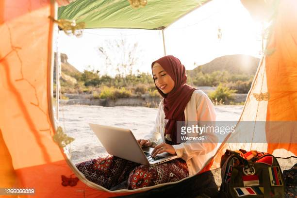 young woman wearing hijab using laptop at a tent - zurückhaltende kleidung stock-fotos und bilder