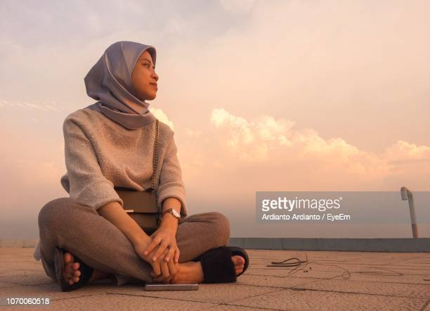 young woman wearing hijab while sitting against sky during sunset - jakarta stock pictures, royalty-free photos & images